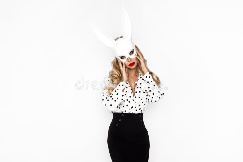 Vackra modemodeller, klädda i konfektyrer i polka prick och påsk bunny mask, över vit bakgrund arkivfoton