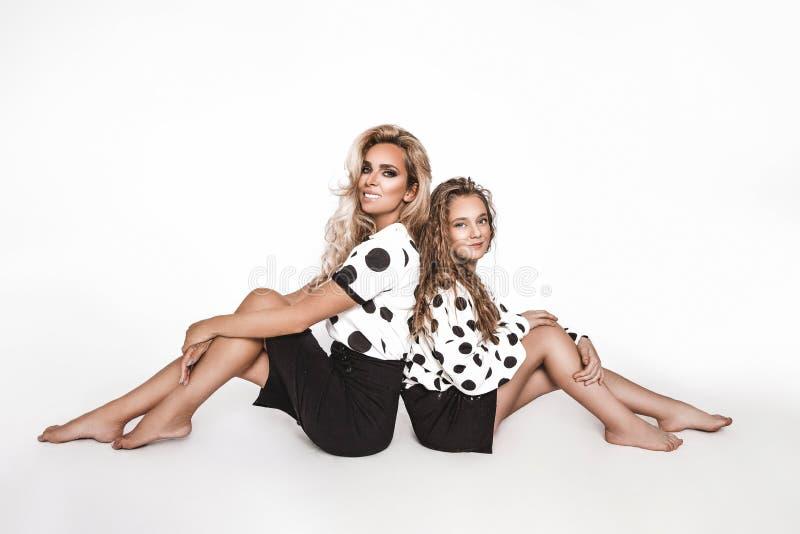 Vackra modemodeller, klädda i svart konfektion i vit prick, över vit bakgrund Mor och royaltyfria bilder