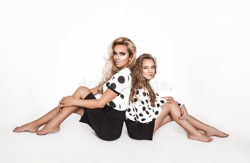 Vackra modemodeller, klädda i svart konfektion i vit prick, över vit bakgrund Mor och royaltyfri foto