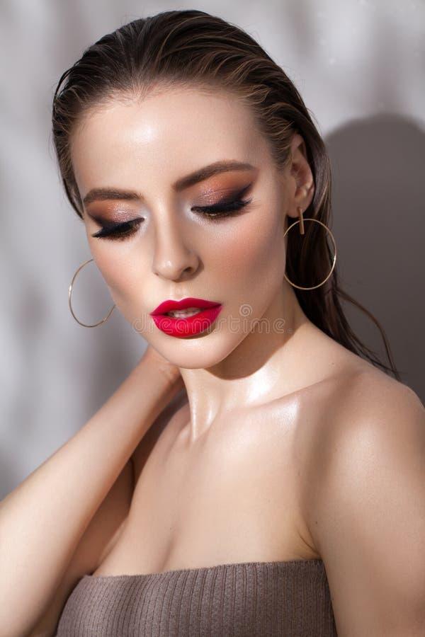Vackra sexiga flickor med professionell kvällsssmink, perfekt skuggande hud, våt hårstrå, rika piskor och trendiga röda läppar arkivbilder