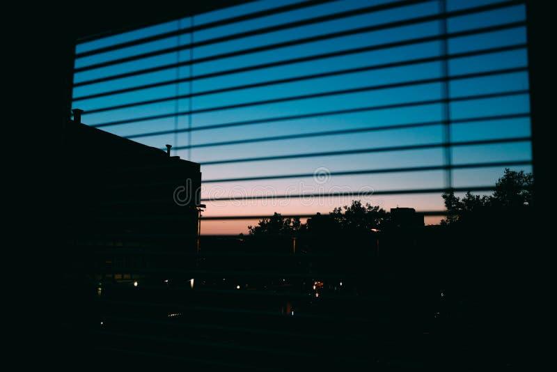 Vackra skott av en stad på natten, tagna genom fönsterblinkar arkivbilder