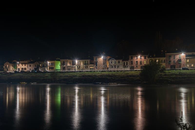 Vackra skott av lägenhetsbyggnader med ljus på natten reflekterade i sjön i Pavia, Italien royaltyfria bilder
