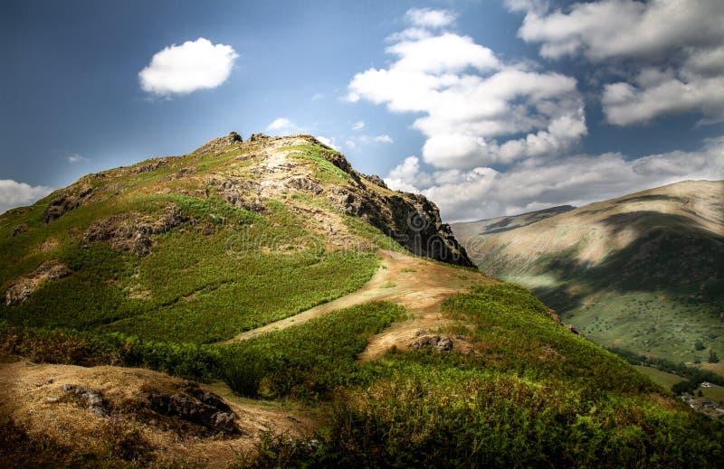 Vackra solljus döpta med 'Lion and the Lamb' bergsratten och Helm Crag-spåret i Cumbria-sjödistriktet royaltyfri foto