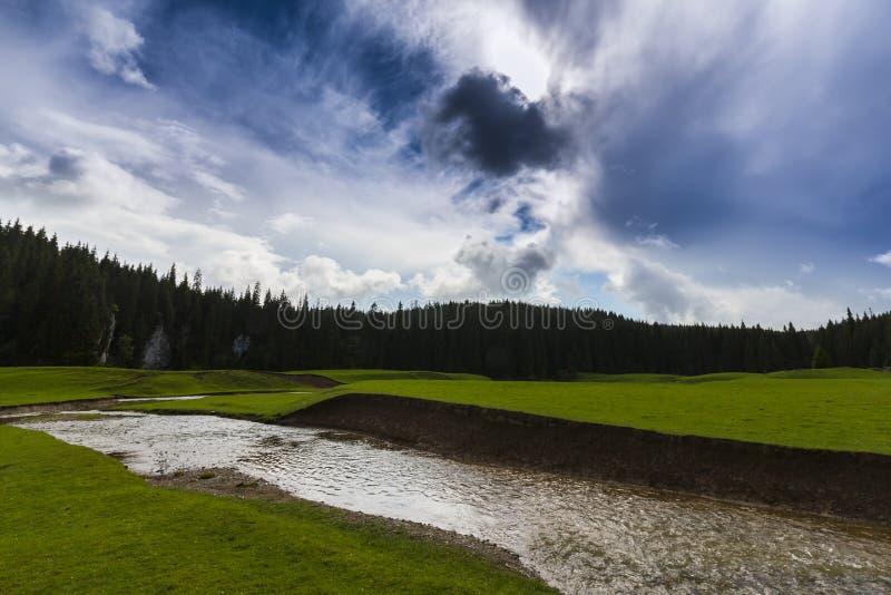Vackra sommarlandskap i avlägsna landsbygdsområden i Europas berg, med stormmoln arkivfoto