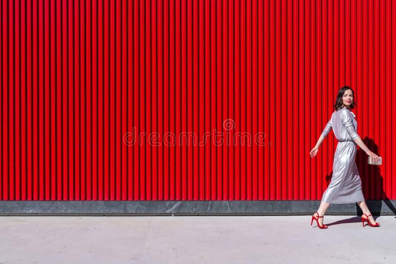 Vackra tjejen på den röda väggen utomhus royaltyfri foto