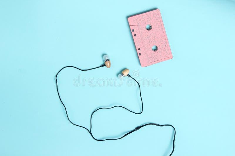 Vacuümoortelefoons op blauwe pastelkleurachtergrond Retro media, muziekminnaar, de jaren '80 De hoogste vlakke mening, legt stock foto's
