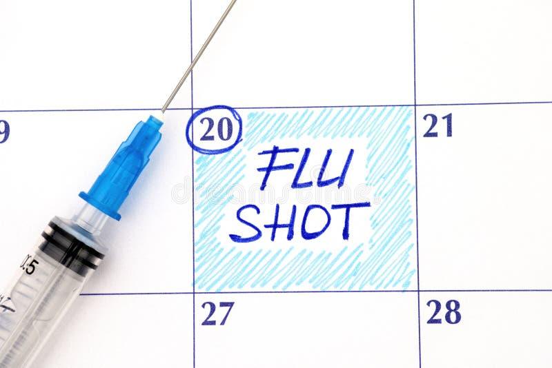 Vacuna contra la gripe del recordatorio en calendario con la jeringuilla imágenes de archivo libres de regalías