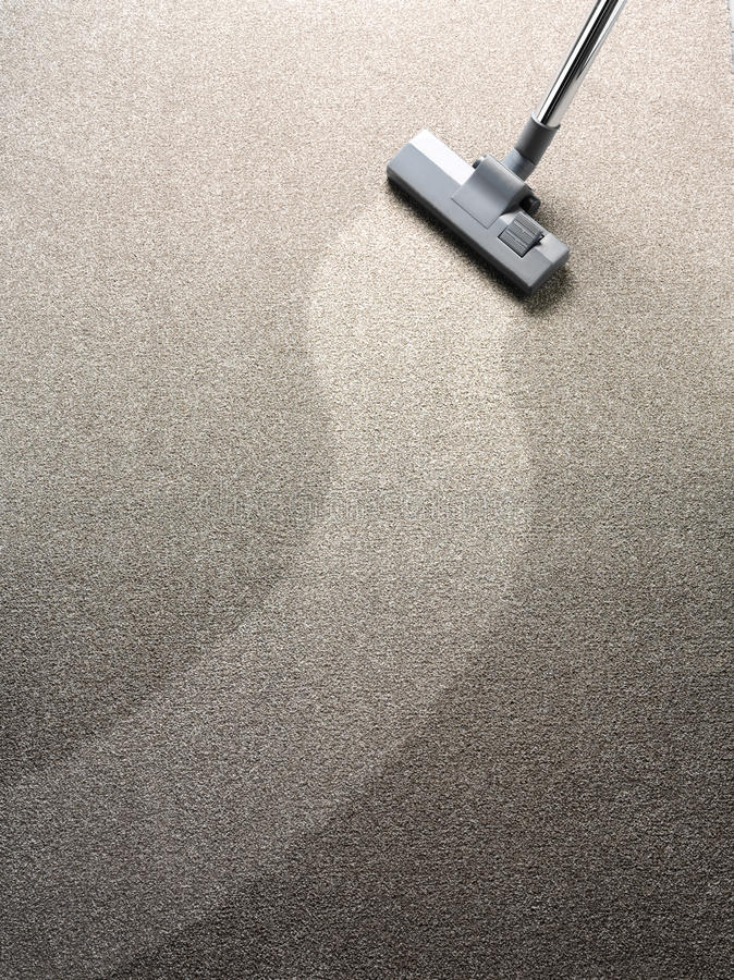 Vacuum cleaner on a carpet with a clean strip for copy space. Vacuum cleaner on a carpet with an extra clean strip for copy space stock photography