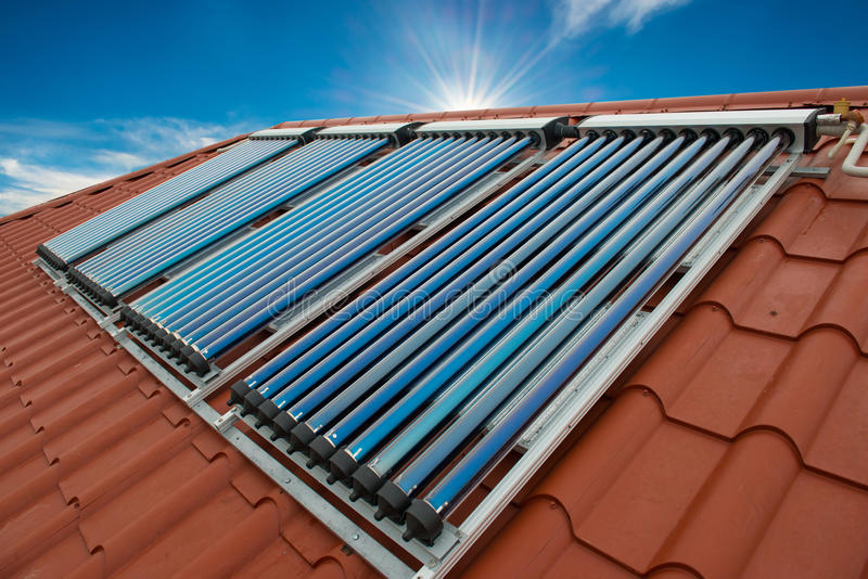 Vacuum collectors- solar water heating system. On red roof of the house stock photography