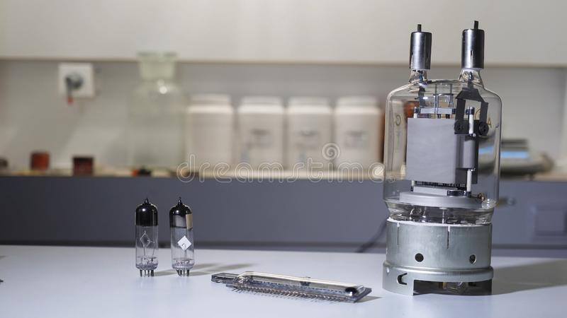 Vacuum electronic lamp with bulbs. Vintage large vacuum tube that lights up from her desk in lab. Scientist in glove. Puts light bulb from vacuum electronic stock photo