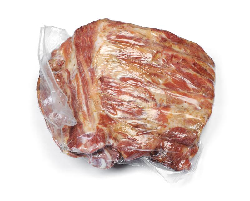 Vacuum packed smoked pork ribs. Meat isolated on white background royalty free stock image