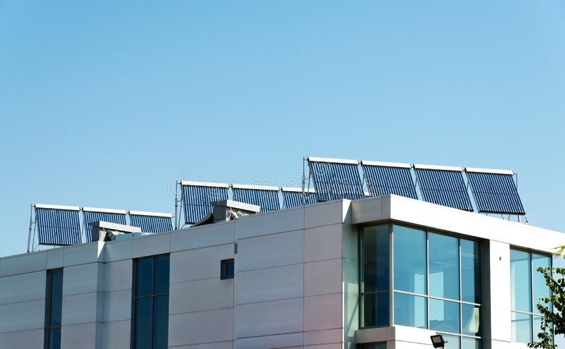 Vacuum solar cell for water heating system on the modern building roof. Green energy, alternative heating and energy supply stock images