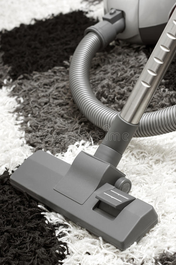 Vacuuming. Vacuum nozzle lying on the carpet in a state of vacuum stock image