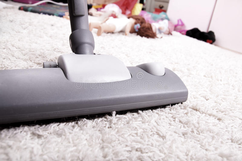 Vacuuming. Cleaning and vacuuming in children room royalty free stock image
