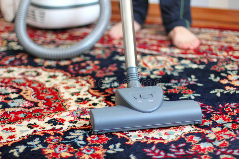 Vacuuming the carpet. Brush vacuum cleaner close-up on the carpet royalty free stock photography