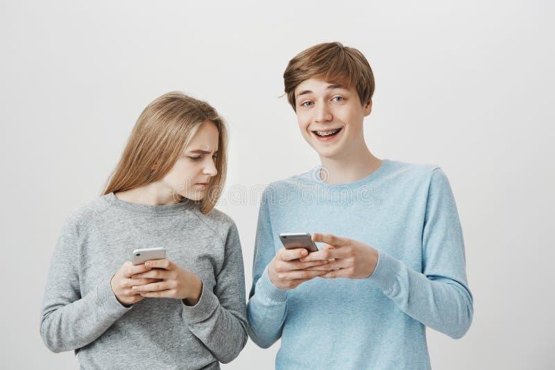 Vad är du som skrattar på Stående av den stiliga högväxta pojkvännen som ler och skrockar, medan rymma smartphonen som håller ögo arkivfoton