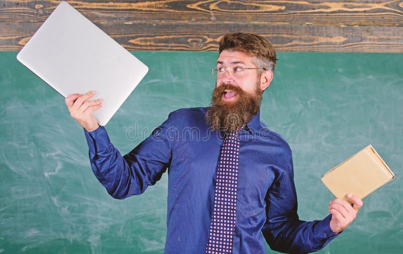 Vad dig skulle föredra Lärare uppsökte hipsterhåll bok och bärbar dator Lärare som väljer modern undervisninginställning Papper royaltyfri foto