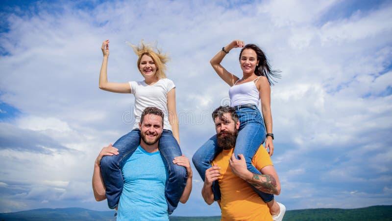 Vad vi skulle kalla gyckel Lyckliga män som piggybacking deras flickvänner Förälskat le för skämtsamma par på molnig himmel älska royaltyfria foton