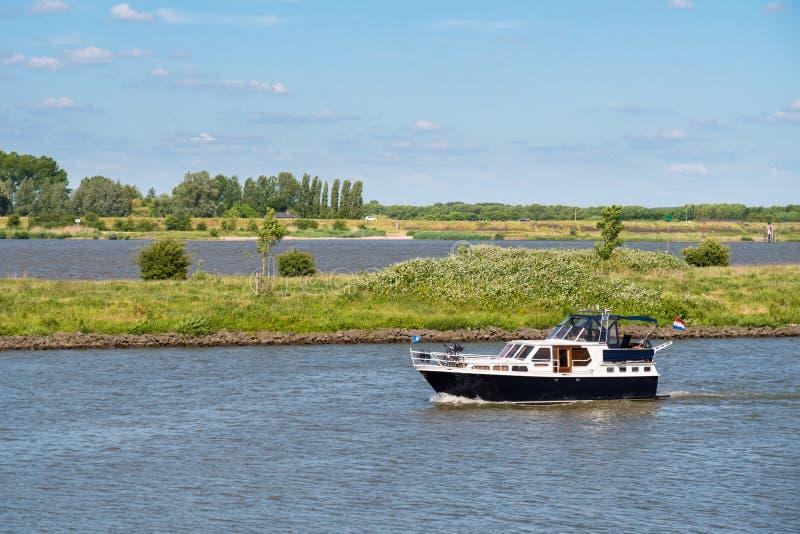 Vada in automobile l'yacht sul fiume Afgedamde Mosa vicino a Woudrichem, Paesi Bassi fotografia stock libera da diritti
