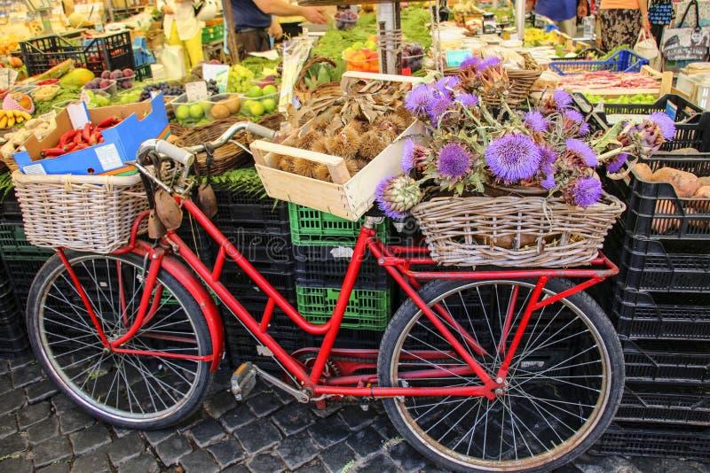 Vada in bicicletta con i canestri delle castagne e dei carciofi sul mercato o immagini stock