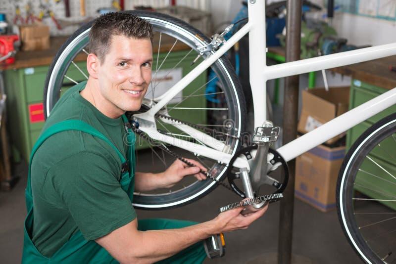 Vada in bicicletta il meccanico che ripara la cinghia del dente in un'officina fotografia stock libera da diritti