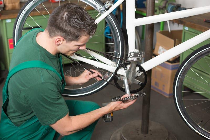 Vada in bicicletta il meccanico che ripara la cinghia del dente in un'officina fotografia stock