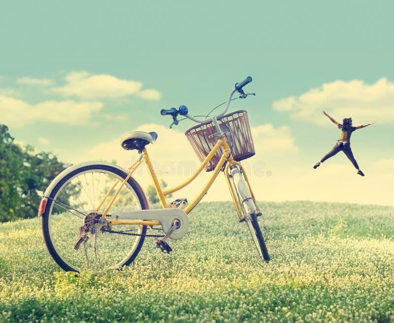 Vada in bicicletta sul giacimento e sull'erba di fiore bianco in natura b del sole immagini stock libere da diritti