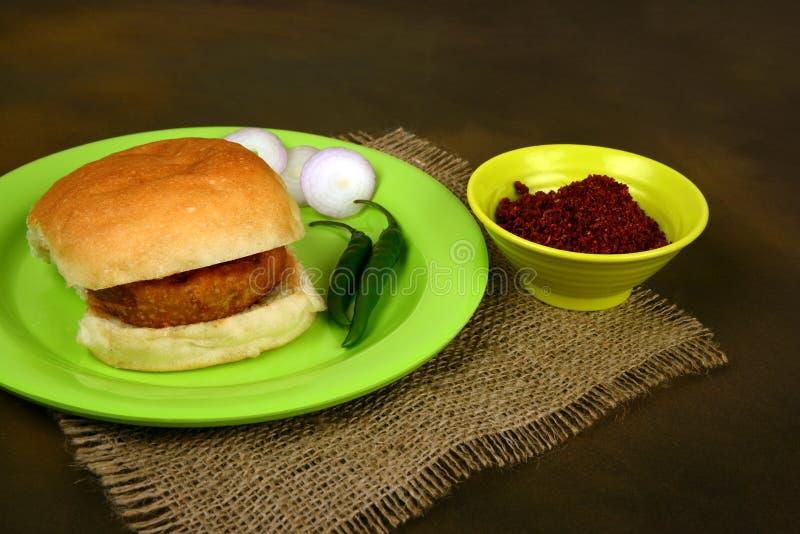 Vada Pav com fatias da cebola, o pimentão verde e o chutney do alho, um alimento popular da rua na Índia foto de stock