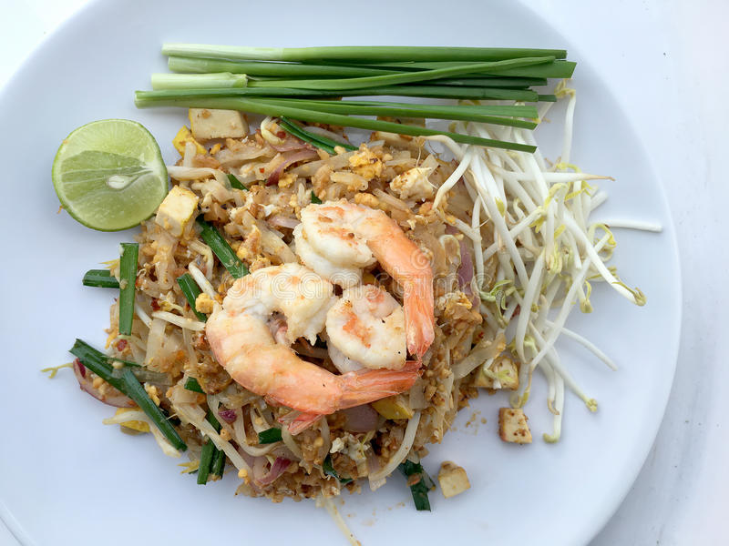 Vaddera thailändska stekte under omrörning risnudlar med räka i den vita maträtten på vit bakgrund Den av Thailand& x27; s-medbor fotografering för bildbyråer