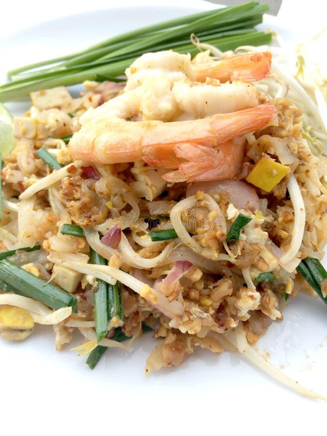 Vaddera thailändska stekte under omrörning risnudlar med räka i den vita maträtten på vit bakgrund Den av Thailand& x27; s-medbor arkivfoton