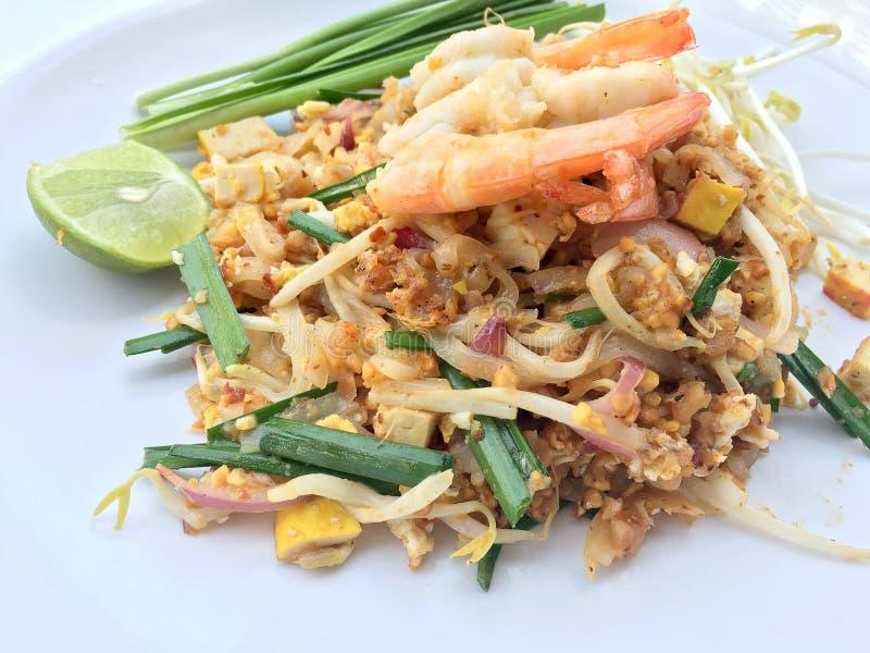 Vaddera thailändska stekte under omrörning risnudlar med räka i den vita maträtten på vit bakgrund Den av Thailand& x27; s-medbor arkivbilder