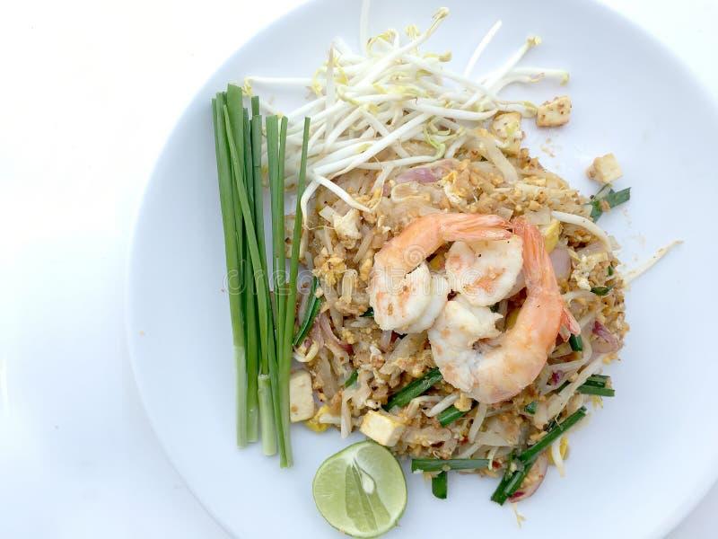 Vaddera thailändska stekte under omrörning risnudlar med räka i den vita maträtten på vit bakgrund Den av Thailand& x27; s-medbor arkivfoto