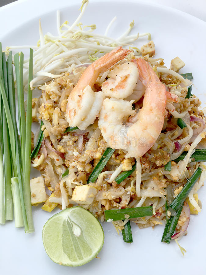 Vaddera thailändska stekte under omrörning risnudlar med räka i den vita maträtten på vit bakgrund Den av Thailand& x27; s-medbor royaltyfria bilder