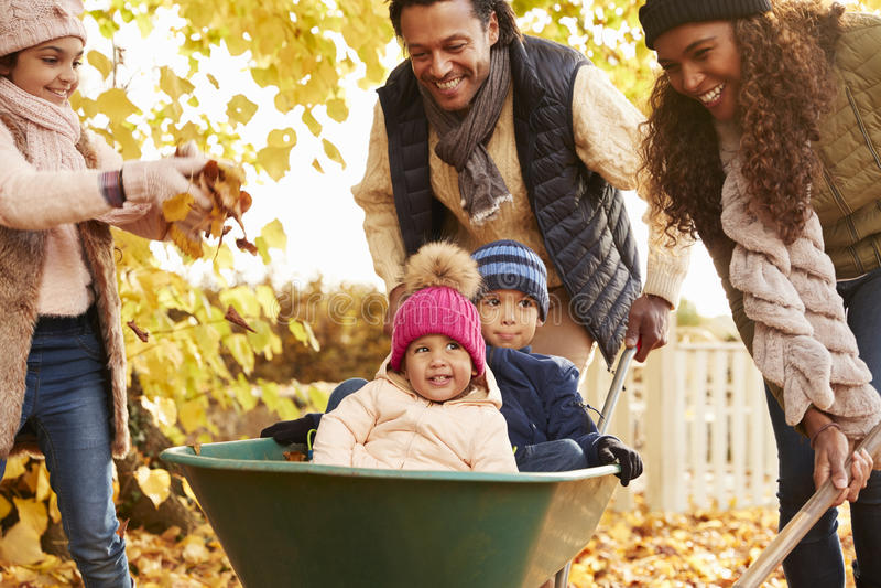 Vader In Autumn Garden Gives Children Ride in Kruiwagen royalty-vrije stock afbeeldingen
