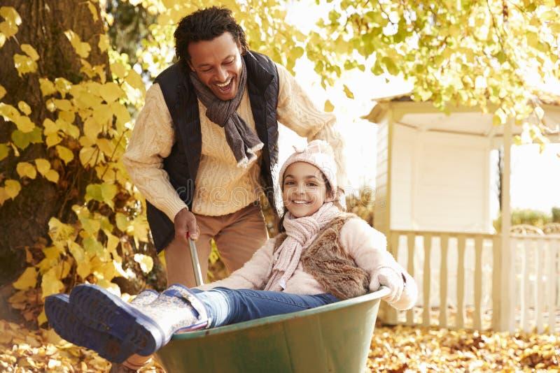 Vader In Autumn Garden Gives Daughter Ride in Kruiwagen stock afbeeldingen