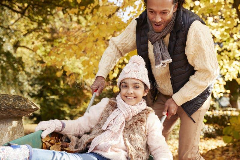 Vader In Autumn Garden Gives Daughter Ride in Kruiwagen stock foto