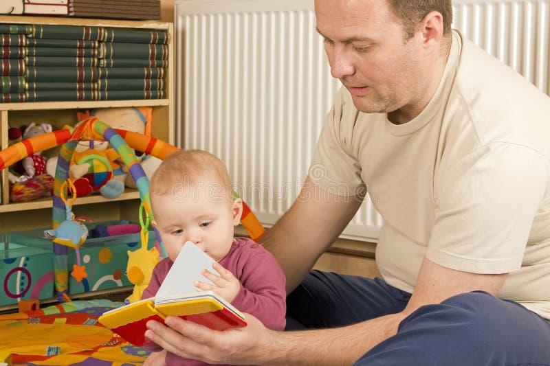 Vader, baby en een boek royalty-vrije stock foto
