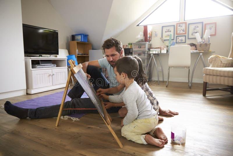 Vader And Children Drawing op Bord in Speelkamer stock foto's