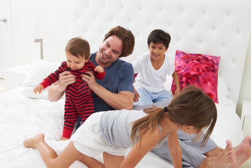 Vader And Children Relaxing in Bed samen stock fotografie