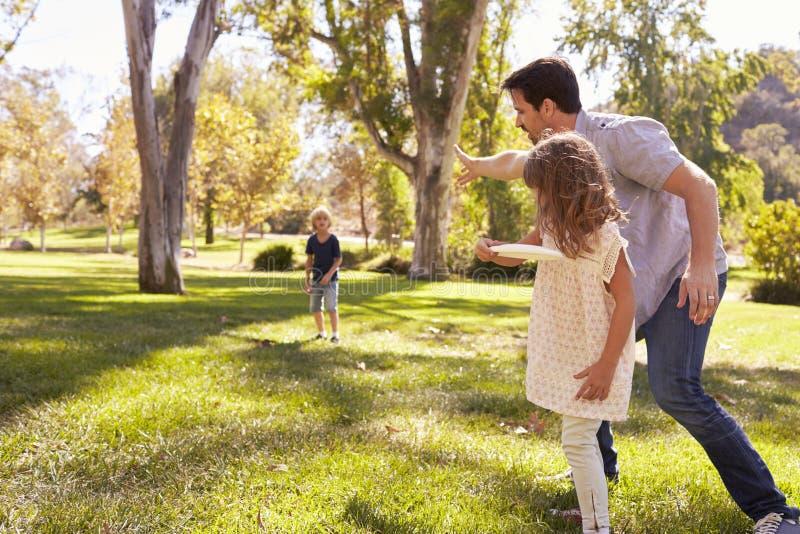 Vader With Children Throwing Frisbee in Park samen royalty-vrije stock foto