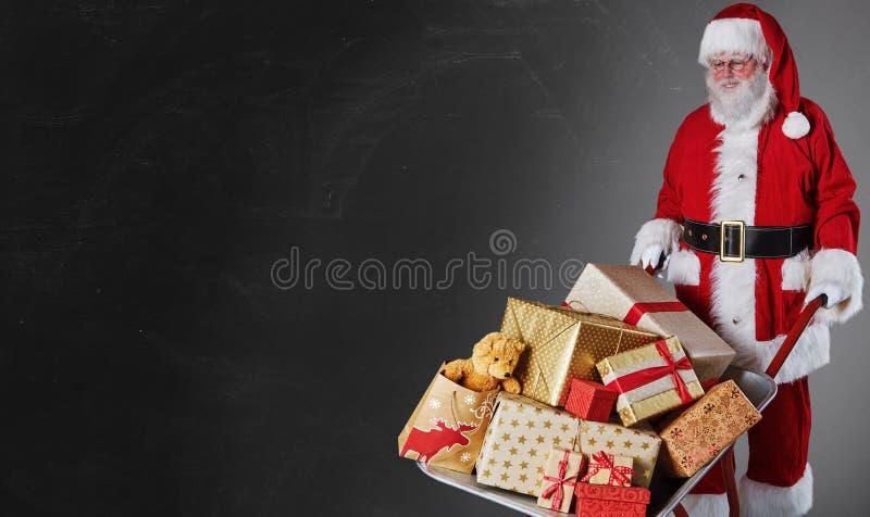 Vader Christmas die een kruiwagenhoogtepunt van gift-verpakt decoratief de leveren stelt over een donkere grijze achtergrond met  royalty-vrije stock foto