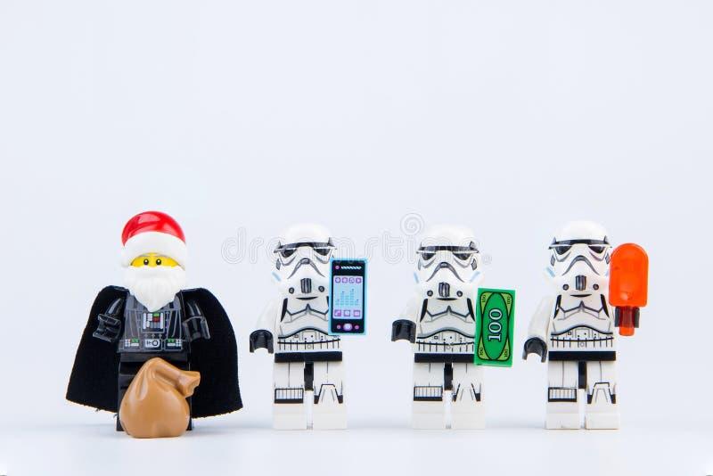 Vader del darth de Lego vestido como Santa Claus que da los regalos al stormtrooper de las Guerras de las Galaxias de Lego imagen de archivo