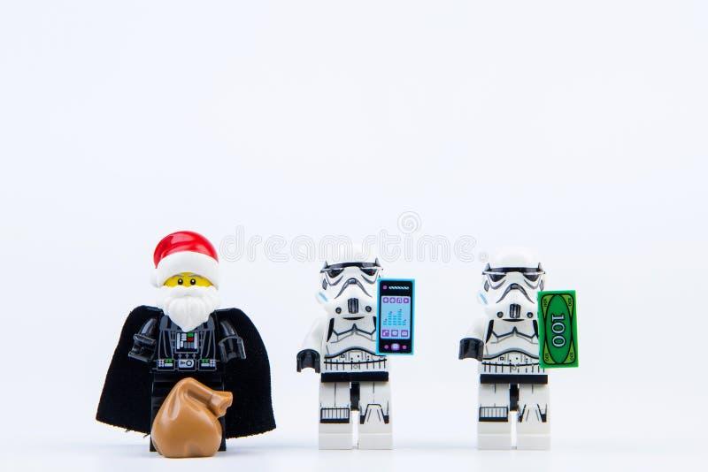 Vader del darth de Lego vestido como Santa Claus que da los regalos al stormtrooper de las Guerras de las Galaxias de Lego foto de archivo