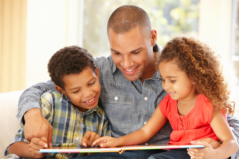 Vader die aan kinderen leest stock fotografie