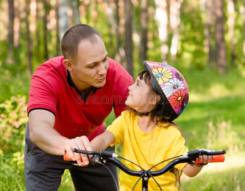 Vader die aan zijn dochter spreken, wat onderwijst om een fiets te berijden royalty-vrije stock foto