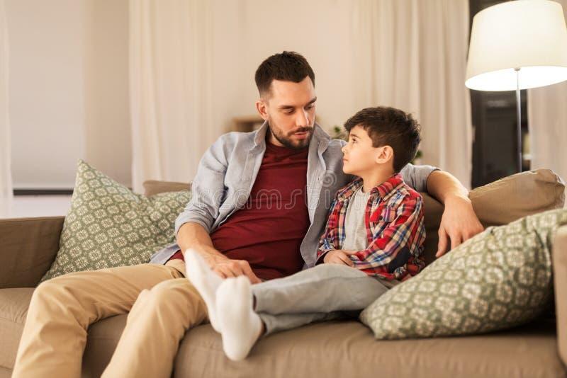 Vader die aan zijn droevige kleine zoon thuis spreken stock afbeeldingen