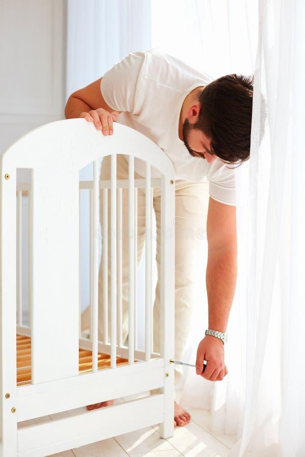 Vader die de voederbak installeren, die voor een nieuwe baby voorbereidingen treffen in de familie stock afbeeldingen