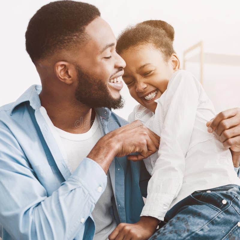 Vader die dochter kietelen, die samen thuis spelen stock foto's