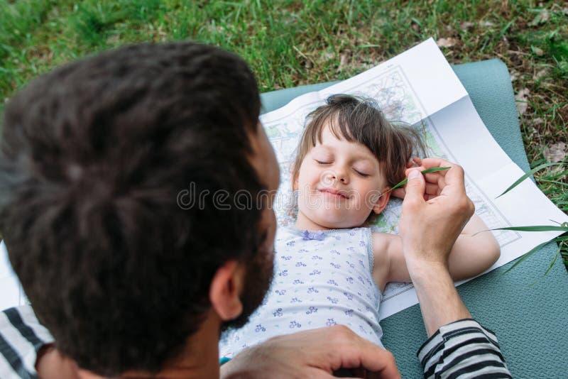 Vader die dochter met gras kietelen royalty-vrije stock fotografie