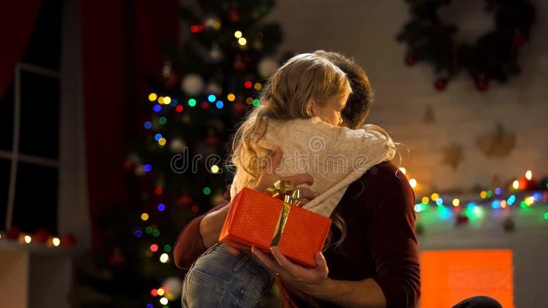 Vader die dochter omhelzen, die haar Kerstmisheden, familietraditie geven stock afbeeldingen